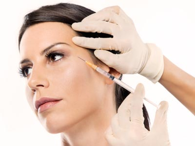 aesthetic wrinkle relaxing treatment with botox being injected into a woman's face