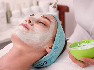 facial chemical peel treatment on lying down woman